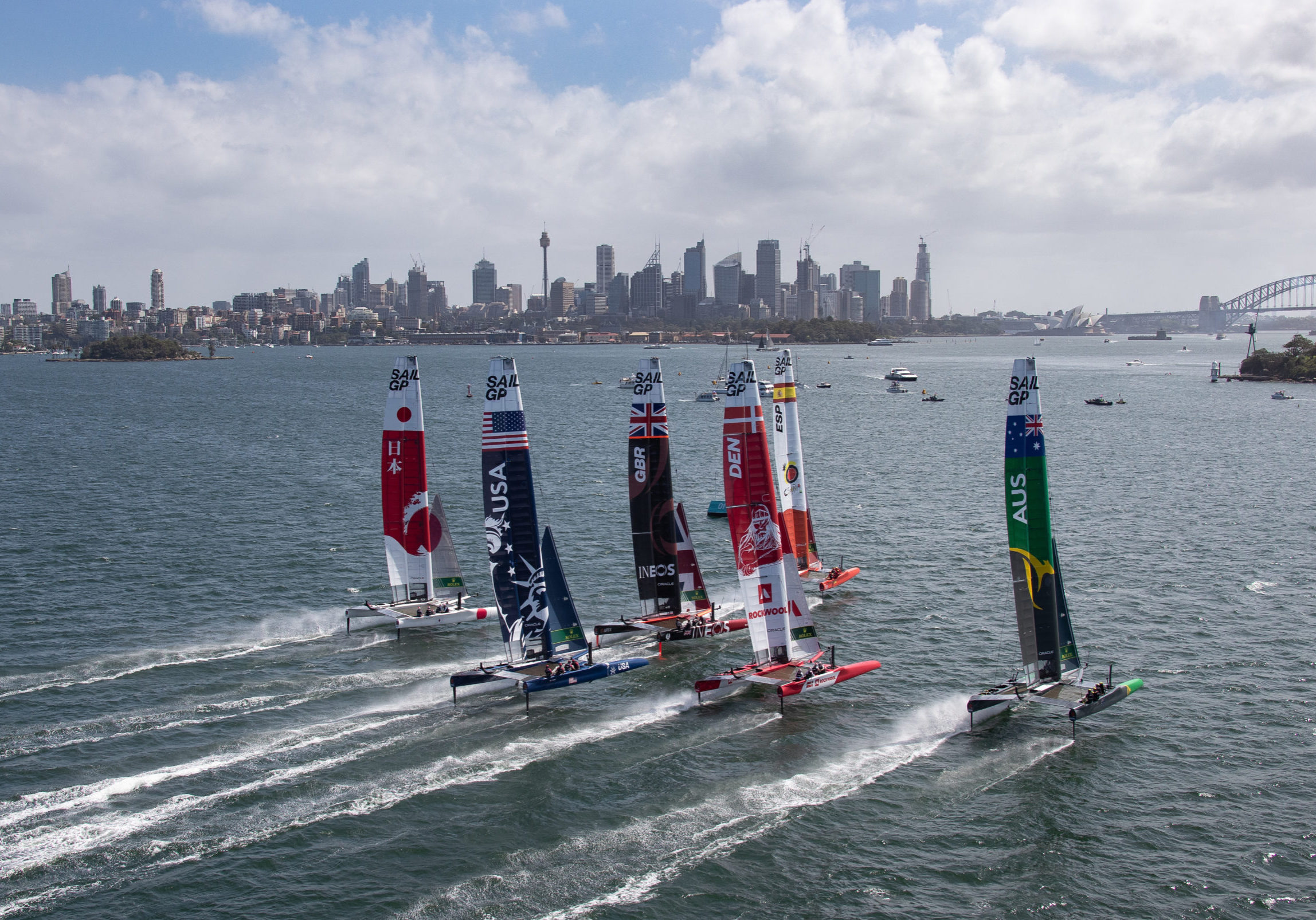 Aerial view of the fleet racing side by side with Sydney Harbour Bridge in the distance, during practice ahead of the Sydney SailGP, Event 1 Season 2 in Sydney Harbour, Sydney, Australia. 27 February 2020. Photo: David Gray for SailGP. Handout image supplied by SailGP